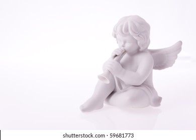 Macro photography of porcelain figurine of angel playing trumpet.