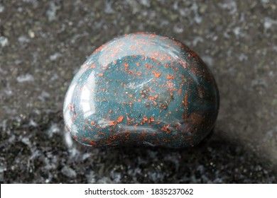 macro photography of sample of natural mineral from geological collection - polished Heliotrope (Bloodstone) gemstone on black granite background