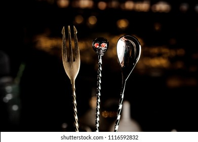 Macro photograpy of unusual cutlery utensils: spoon, fork and skull-shaped spoon arranged in line on the background of bar lights
