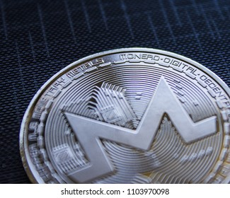 Macro physical Coin cryptocurrency Monero on blue background.