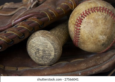 a macro picture of a baseball, glove, and bat