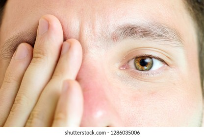 a macro picture of an eye while the other eye  covered by the caucasian male model's hand