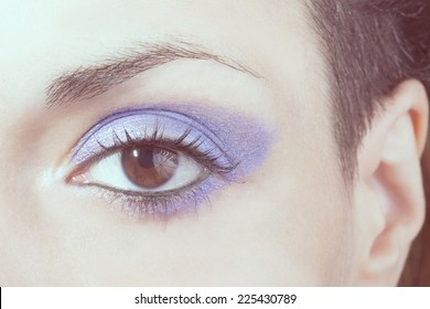 Macro picture of the eye of a woman with blue make-up