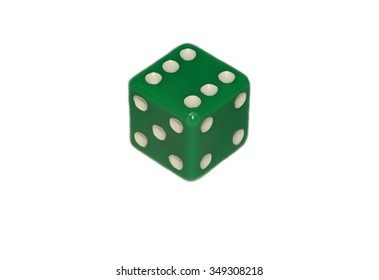 Macro picture of a green dice with white dots in isolated white background.