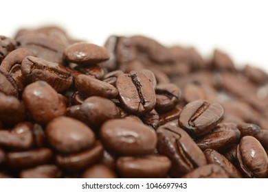Macro of a pile of roasted coffee beans, on a white background
