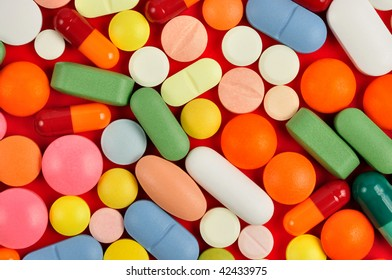 Macro of pills and capsules on red background