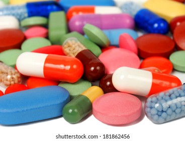 Macro of pills and capsules on white background, focus on nearest ones.