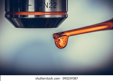 Macro of a pipette adding a drop of fluid to one of several cylindrical phials Vintage