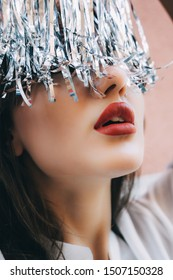 Macro portrait of girl with big red plump lips in white blouse, gold earrings and silver metal foil tinsel strips like fringe hair. Beauty concept for new year. Pure perfect skin woman.