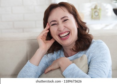 Macro portrait of smiling female face. Attractive and beautiful middle aged woman sitting on sofa and relaxing at home. Menopause. Mothers day