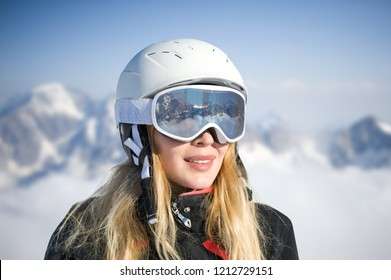 Macro portrait. Young adult woman snowboarder or skier in snow winter on the mountainside the ski mask or goggles reflect the mountains