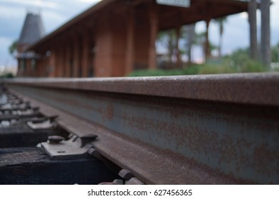Macro of railroad track with station in the background and rail in the foreground.
