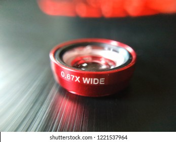Macro of a red colour mobile phone wide angle lens attachment with blurred background.