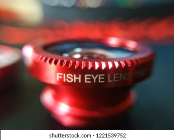 Macro of a red colour mobile phone fish eye lens attachment with blurred background.