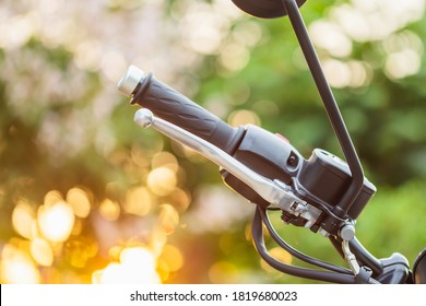 Macro right handle bar with hand brake of motorcycle. Motorcycle maintenance concept outdoor shooting with sunset effect