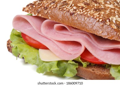 macro sandwich with ham, cheese, tomatoes and lettuce, sprinkling sesame seeds isolated on white background close-up.