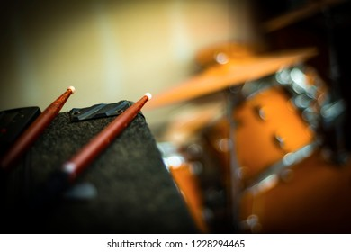 A macro shallow focus shot of worn and pitted drum stick tips lying on a black amplifier with a maple drum set out of focus in the background. The concept is practicing the drums is hard work.