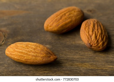 Macro of shelled almond kernels with selective focus on wood background