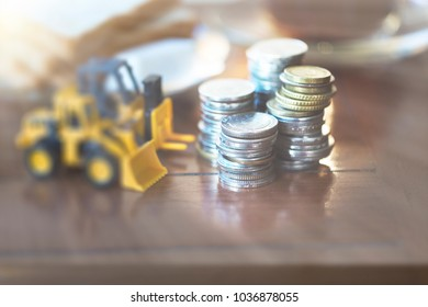 Macro shoot of major currency money including euro, us dollar and Chinese Yuan (RMB), Mixed stacked Coins, on wooden table, with blur construction machinery toy. Saving money concept. Vintage tone.