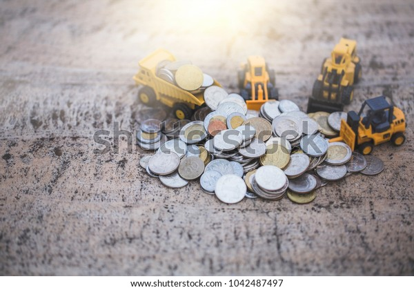 Macro shoot of major currency money including euro, us dollar and Chinese Yuan (RMB), Mixed stacked Coins, on mable table, with blur construction machinery toy. Saving money concept. Vintage tone.