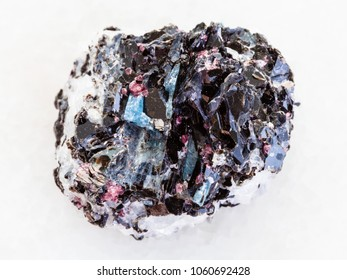 macro shooting of natural mineral rock specimen - rough Gneiss stone with biotite, kyanite, tourmaline crystals on white marble background from Hit-island of Upper Pulongskoye Lake, Karelia in Russia