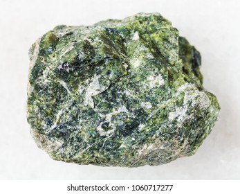 macro shooting of natural mineral rock specimen - rough serpentine stone on white marble background
