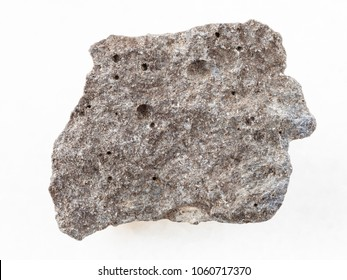 macro shooting of natural mineral rock specimen - piece of gray basalt stone on white marble background