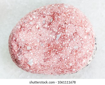 macro shooting of natural mineral rock specimen - pebble of pink Arkose sandstone on white marble background