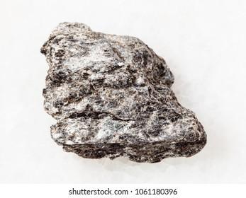 macro shooting of natural mineral rock specimen - rough quartz-biotite schist stone on white marble background