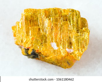 macro shooting of natural mineral rock specimen - raw native orpiment stone on white marble background from Yakutia, Russia