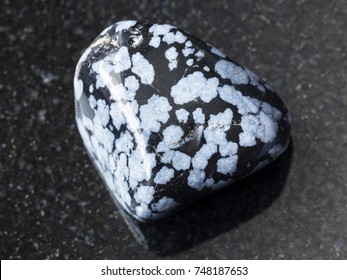 macro shooting of natural mineral rock specimen - tumbled snowflake obsidian gem stone on dark granite background from USA