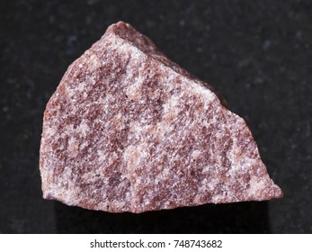 macro shooting of natural mineral rock specimen - rough pink Quartzite stone on dark granite background