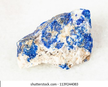 macro shooting of natural mineral - rough Lazurite (Lapis Lazuli) stone on white marble from Ural Mountains