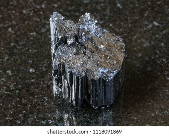 macro shooting of natural rock specimen - raw crystal of black Tourmaline (Schorl) stone on dark granite background