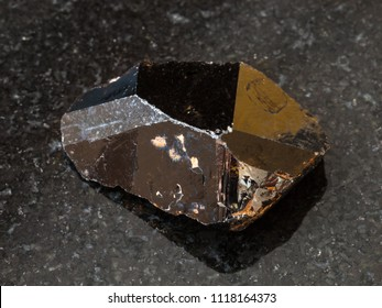 macro shooting of natural rock specimen - crystal of Cassiterite (Tin ore) stone on black granite background from Pravourmiyskoe deposit in Khabarovsk Krai, Russia