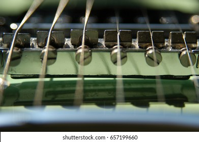 Macro shot of 6 string electric guitar strings and pickups, focus on the strings. Detail of electric guitar strings. Vintage light green guitar.