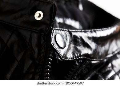 Macro shot of black leather jacket focusing on zipper and stud