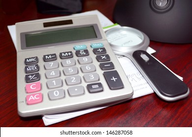 Macro shot of a calculator and paper over a wooden desk