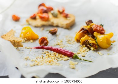 Macro shot of chilli pepper on backing paper with roasted toast and tomato in background horizontal