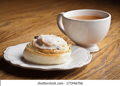 Macro shot of a cinnamon roll on an antique dish next to a cup of hot wassail on a wooden table