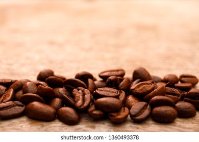 Macro shot of coffee beans on old rustic wooden table and bokeh background with copy space for text