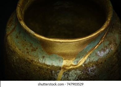A macro shot of a cup repaired with gold powder using the Japanese art form of kintsugi.