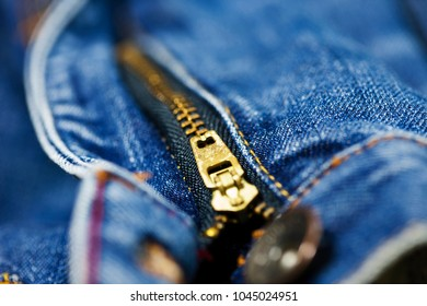 Macro shot of denim jeans focusing on metal zipper