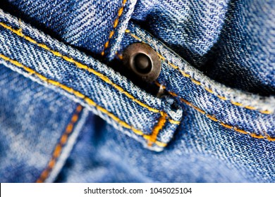 Macro shot of denim jeans showing stitching and metal stud