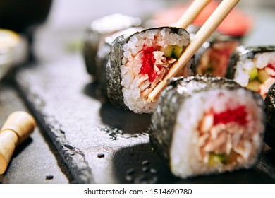 Macro shot of eating sushi roll in Japanese restaurant with chopsticks closeup. Taking portion of sushi rolls with rice, fried salmon, flying fish caviar, cucumber and spicy sauce