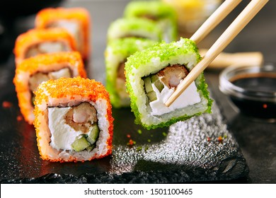 Macro shot of eating uramaki sushi roll with rice, cream cheese, fried shrimp, cucumber, flying fish caviar and nori. Holding fresh colorful rolls in Japanese restaurant with chopsticks closeup