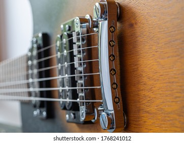 Macro shot of an electric guitar. Strings and bridge. Wooden body of the guitar Music equipment. Metal strings