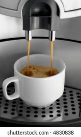 Macro shot of espresso flowing into a cup.