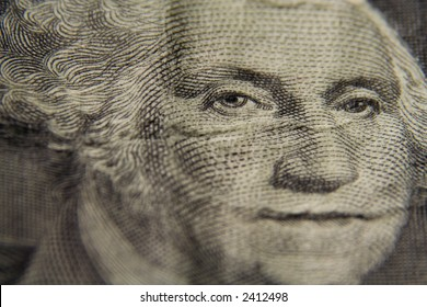 A macro shot of the face of George Washington on a one dollar bill