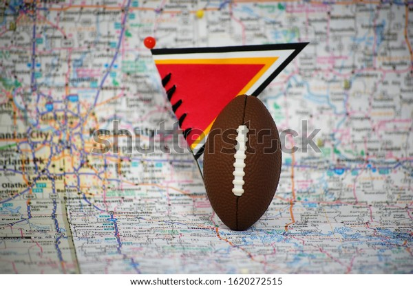 Macro shot of a flag and football on Kansas City, Missouri in a map.